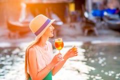 Frau mit italienischem Aperitif nahe dem Wasser chanal in Venedig Stockbilder