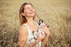 Frau mit Jack Russell-Terrierwelpen auf ihren Händen, Weizenfeld stockfotografie