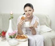 Frau mit Kaffee und Hörnchen Lizenzfreie Stockbilder