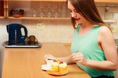 Frau mit Kaffee und Kuchen in der Küche gluttony stockfoto