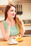 Frau mit Kaffee und Kuchen in der Küche gluttony stockfotografie