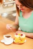 Frau mit Kaffee und Kuchen in der Küche gluttony stockbild