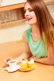 Frau mit Kaffee und Kuchen in der Küche gluttony stockbilder