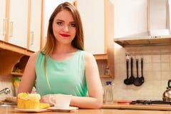 Frau mit Kaffee und Kuchen in der Küche gluttony lizenzfreies stockfoto