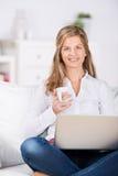 Frau mit Kaffee und Laptop auf Sofa Stockbilder
