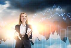 Frau mit Kaffee und Notizbuch und Diagramme im Himmel Lizenzfreies Stockfoto