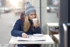 Frau mit Kaffee und Zeitung draußen Lizenzfreie Stockbilder