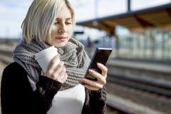 Frau mit Kaffeetasse unter Verwendung des Handys an der Bahnstation Stockbild