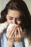 Frau mit kaltem haltenem Gewebe und dem Niesen Lizenzfreie Stockbilder