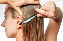 Frau mit Kamm wendet Pflegespülung auf ihrem nassen blonden Haar an stockfotografie