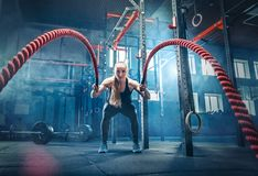 Frau mit Kampfseilkampf ropes Übung in der Eignungsturnhalle stockbild