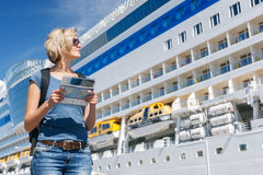 Frau mit Karte, vor Kreuzfahrtschiff stockfoto