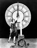 Frau mit Kerze und Uhr auf Sylvesterabenden Lizenzfreie Stockfotos