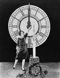 Frau mit Kerze und Uhr auf Sylvesterabenden (alle dargestellten Personen sind nicht längeres lebendes und kein Zustand existiert  Stockfotos