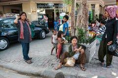 Frau mit Kind in ihren Armen Straße, mehrere sind dety und Frauen lizenzfreies stockbild