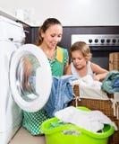 Frau mit Kind nahe Waschmaschine Stockfoto