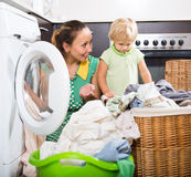 Frau mit Kind nahe Waschmaschine Lizenzfreie Stockfotos