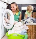 Frau mit Kind nahe Waschmaschine Lizenzfreie Stockfotografie
