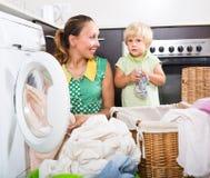 Frau mit Kind nahe Waschmaschine Stockbild