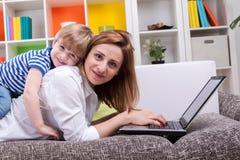 Frau mit Kinderlüge auf Sofa Stockfotografie