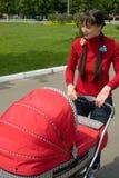 Frau mit Kinderwagen lizenzfreie stockfotos