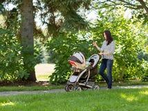 Frau mit Kinderwagen unter Verwendung des Handys im Park Lizenzfreie Stockbilder
