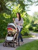 Frau mit Kinderwagen unter Verwendung des Handys im Park Stockbild
