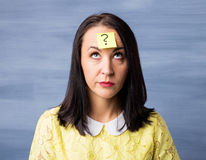 Frau mit klebriger Anmerkung über ihre Stirn mit Fragezeichen Stockbild