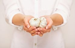 Frau mit Knoblauchzehen in den Händen lizenzfreies stockbild