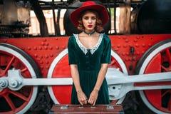 Frau mit Koffer gegen Dampflokomotive Stockbild