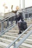 Frau mit Koffer gehend hinunter Treppe an der Bahnstation Lizenzfreie Stockfotos