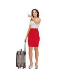 Frau mit Koffer ihren Finger zeigend Stockbild