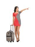 Frau mit Koffer ihren Finger zeigend Stockfotos