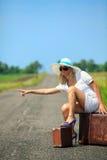 Frau mit Koffer stoppt das Auto Lizenzfreies Stockbild