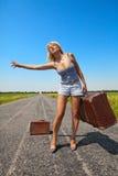 Frau mit Koffer stoppt das Auto Stockbilder