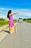 Frau mit Koffer trampend Stockfoto