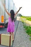 Frau mit Koffer trampend Lizenzfreies Stockfoto