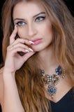 Frau mit Kontaktlinse des grünen Auges, dem langen Haar und großer Halskette Lizenzfreies Stockbild