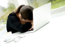 Frau mit Kopf auf Laptop Lizenzfreies Stockbild