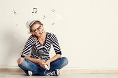Frau mit Kopfhörer an der Wand Stockfotografie
