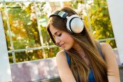 Frau mit Kopfhörern auf dem Schauen entspannt lizenzfreies stockfoto