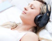 Frau mit Kopfhörern auf dem Schlafen Lizenzfreie Stockfotografie