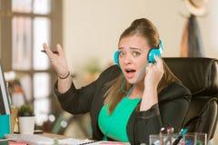 Frau mit Kopfhörern laut singend an ihrem Schreibtisch lizenzfreie stockbilder