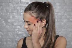 Frau mit Kopfschmerzen, ihren Kopf halten, Schmerzbereich markiert im Rot stockfotografie