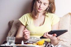 Frau mit Kopfschmerzen und einer Grippe im Bett wird mit Tabletten und Vitaminen behandelt Saisonkälten im Winter stockfotos