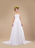 Frau mit Kranz von Blumen im weißen Kleid Stockbild