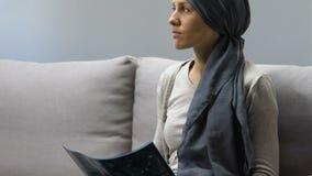 Frau mit Krebs, der das Gehirnröntgenstrahlbild, deprimiert durch tödliche Diagnose betrachtet stock footage