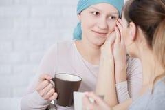 Frau mit Krebssitzung mit Freund stockbild