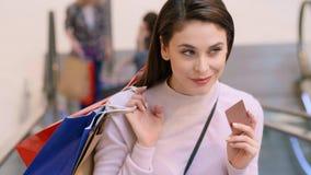 Frau mit Kreditkarte und Einkaufstaschen während des großen Einkaufens stock video