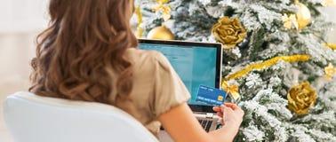 Frau mit Kreditkarte und Laptop vor Weihnachtsbaum stockfotos